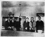 Six men posed with transmitting equipment by St. Norbert Abbey